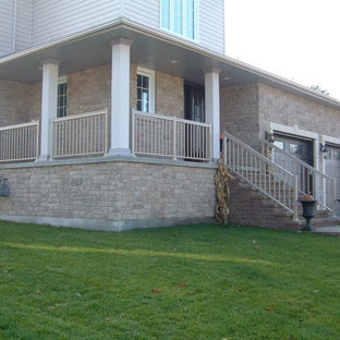 This is an example of a mid-sized traditional front porch design in Toronto with a roof extension.