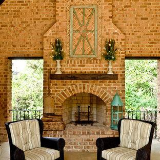 Idee per un grande patio o portico chic dietro casa con un focolare, pavimentazioni in pietra naturale e un tetto a sbalzo