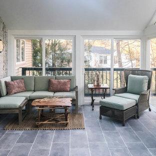 Immagine di un portico tropicale di medie dimensioni e dietro casa con pavimentazioni in pietra naturale e un tetto a sbalzo