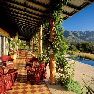 This is an example of an eclectic tile porch design in Santa Barbara with a roof extension.