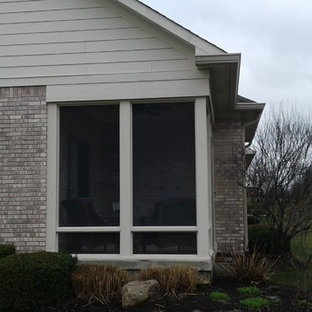 This is an example of a small traditional concrete screened-in back porch design in Indianapolis with a roof extension.