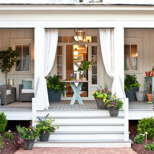 Ejemplo de terraza clásica, de tamaño medio, en patio delantero y anexo de casas, con entablado y jardín de macetas