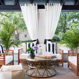 На фото: большая веранда на переднем дворе в средиземноморском стиле с крыльцом с защитной сеткой, покрытием из бетонных плит и навесом с