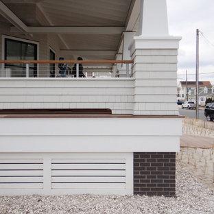 Idee per un ampio portico stile marinaro davanti casa con pedane, un tetto a sbalzo e parapetto in cavi