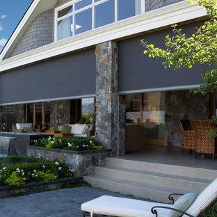 Esempio di un grande portico stile rurale dietro casa con pavimentazioni in cemento, un tetto a sbalzo e un portico chiuso
