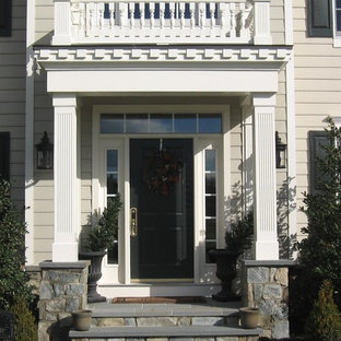 Small arts and crafts stone front porch photo in Baltimore with a roof extension