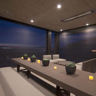 Esempio di un grande portico minimalista dietro casa con piastrelle, un tetto a sbalzo e un focolare