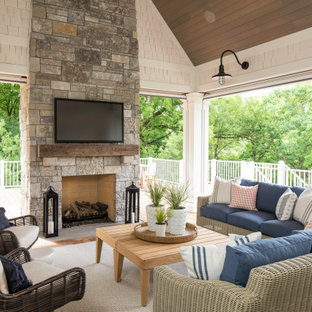 Large transitional back porch idea in Minneapolis with a fireplace, decking and a roof extension
