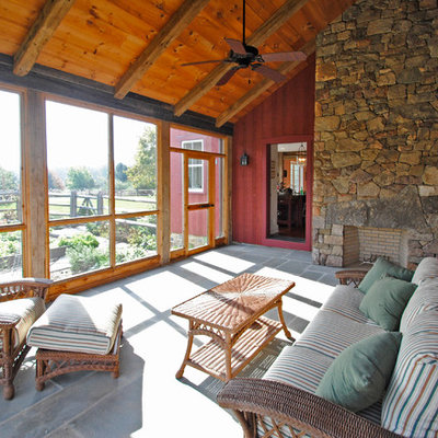 This is an example of a large cottage tile screened-in back porch design in Philadelphia with a roof extension.