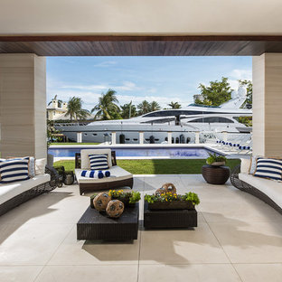 Huge coastal tile porch idea in Miami with a roof extension