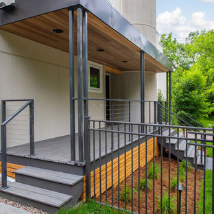 This is an example of a mid-sized modern front porch design in Minneapolis with decking and an awning.