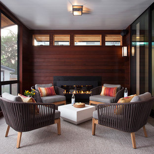 Trendy screened-in back porch idea in Austin with a roof extension