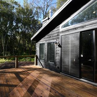Foto di un portico moderno di medie dimensioni e dietro casa con un portico chiuso, pedane e un tetto a sbalzo