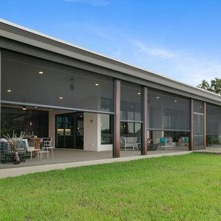 Esempio di un ampio portico design dietro casa con un portico chiuso, lastre di cemento e un tetto a sbalzo