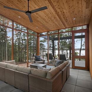 Foto di un grande patio o portico stile rurale nel cortile laterale con un portico chiuso, pavimentazioni in cemento e un tetto a sbalzo
