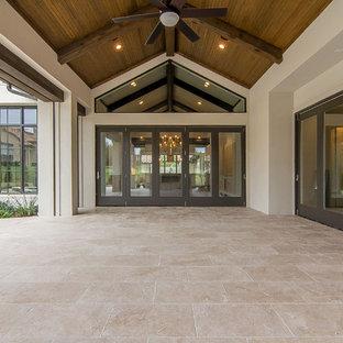 Ispirazione per un grande portico mediterraneo dietro casa con un portico chiuso, pavimentazioni in pietra naturale e un tetto a sbalzo