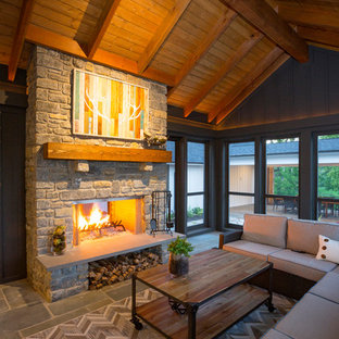 Farmhouse stone screened-in front porch idea in Cincinnati with a roof extension