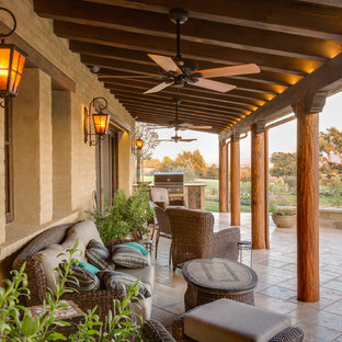 Tuscan outdoor kitchen porch photo in Santa Barbara with a roof extension
