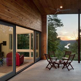 Immagine di un piccolo patio o portico minimal dietro casa con un portico chiuso, lastre di cemento e un tetto a sbalzo