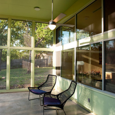 This is an example of a mid-sized contemporary concrete screened-in back porch design in Austin with a roof extension.