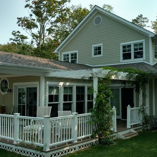 Large classic back porch idea in New York with decking and a pergola