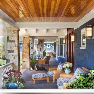 Ispirazione per un grande portico chic davanti casa con un tetto a sbalzo e piastrelle