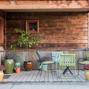 Foto di un piccolo portico rustico davanti casa con un giardino in vaso, pedane e un tetto a sbalzo