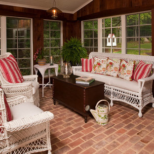 Mountain style brick porch photo in Raleigh with a roof extension