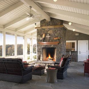 Ispirazione per un portico country con pavimentazioni in pietra naturale, un tetto a sbalzo e con illuminazione