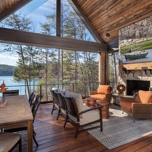 Idéer för en rustik veranda, med en öppen spis och trädäck