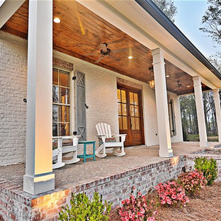 This is an example of a mid-sized farmhouse brick front porch design in Jackson with a roof extension.