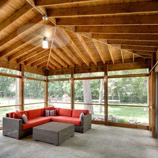Immagine di un portico eclettico di medie dimensioni e dietro casa con un portico chiuso, lastre di cemento e un tetto a sbalzo