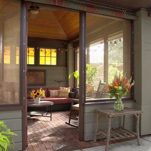 Modelo de porche cerrado de estilo americano, grande, en patio trasero, con adoquines de ladrillo