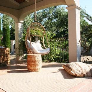 Cette photo montre un porche méditerranéen de taille moyenne avec un foyer extérieur et une extension de toiture.