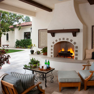 This is an example of a mediterranean porch design in San Diego with a fireplace and a roof extension.
