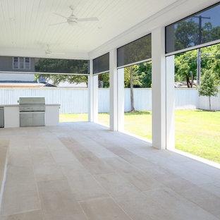 Immagine di un grande portico minimalista dietro casa con un portico chiuso, pavimentazioni in cemento e un tetto a sbalzo