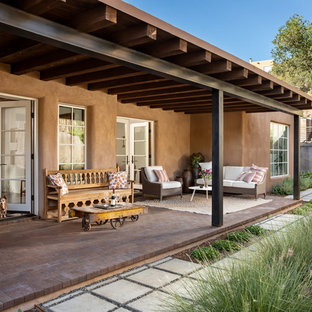 Inspiration for a mid-sized southwestern brick back porch remodel in Albuquerque with a roof extension