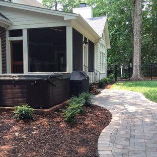 Immagine di un portico classico di medie dimensioni e dietro casa con un portico chiuso, piastrelle e un tetto a sbalzo
