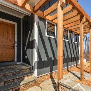 Esempio di un grande portico country davanti casa con pavimentazioni in pietra naturale e una pergola