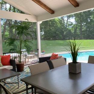 Idee per un portico tropicale di medie dimensioni e dietro casa con un portico chiuso, pedane, un tetto a sbalzo e parapetto in materiali misti
