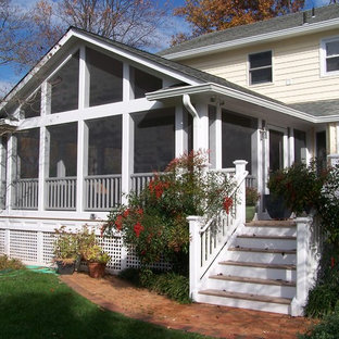 Large classic screened-in back porch idea in DC Metro with decking and a roof extension
