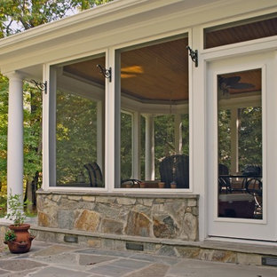 This is an example of a mid-sized traditional stone screened-in back porch design in DC Metro with a roof extension.
