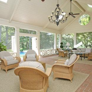 Modelo de terraza clásica, grande, en anexo de casas y patio trasero, con adoquines de ladrillo y chimenea