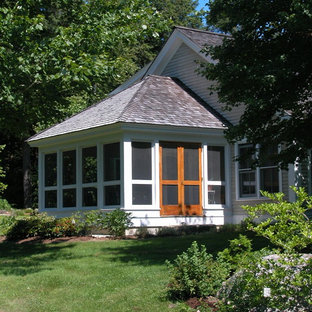 This is an example of a traditional screened-in front porch design in Portland Maine with a roof extension.