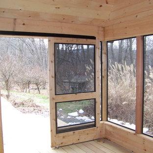 Foto di un patio o portico american style di medie dimensioni e dietro casa con un portico chiuso, pedane e un tetto a sbalzo