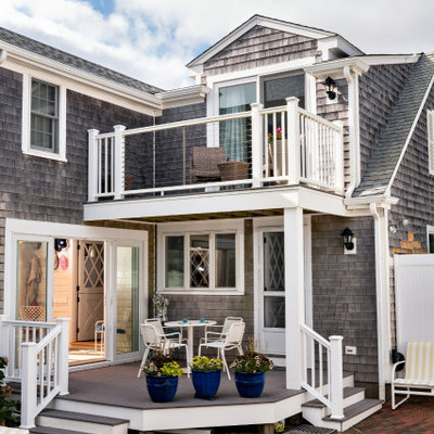 This is an example of a mid-sized coastal brick back porch design in Boston with a roof extension.