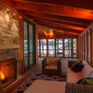 Ispirazione per un grande portico minimalista nel cortile laterale con un focolare, pedane e un tetto a sbalzo