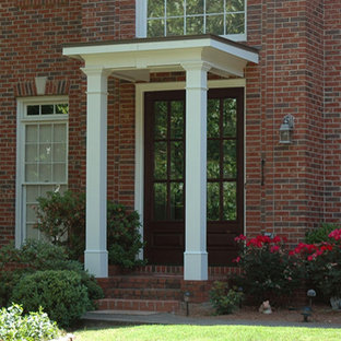 This is an example of a small traditional front porch design in Atlanta with a roof extension.