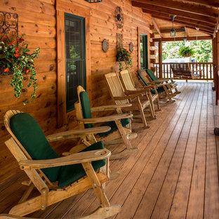 Rustik inredning av en stor veranda framför huset, med trädäck och takförlängning