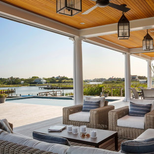 Inspiration for a large beach style outdoor kitchen porch remodel in New York with a roof extension and decking